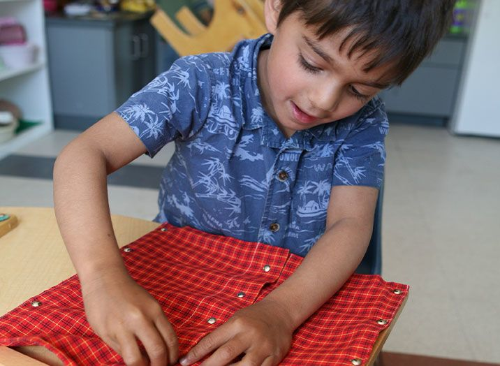 Young boy exploring textures at daycare | Bright Horizons | Montessori