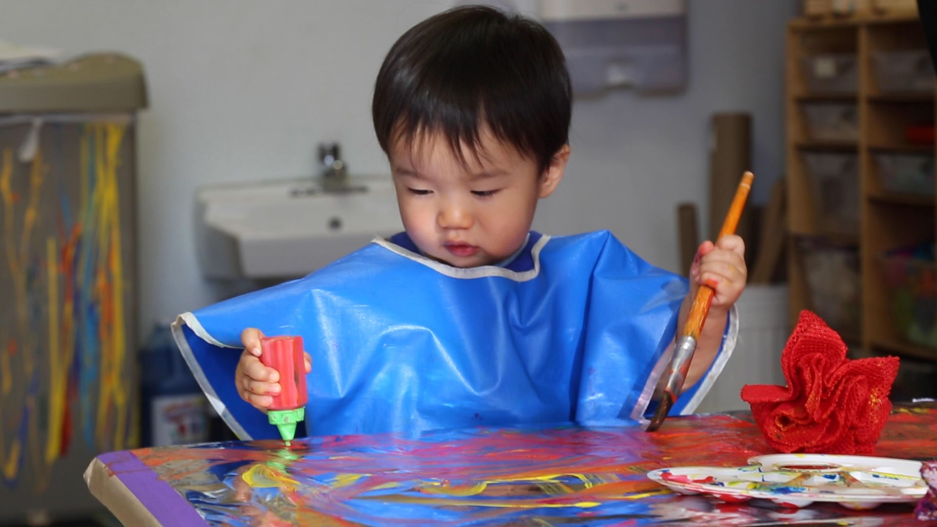 toddler painting in art room