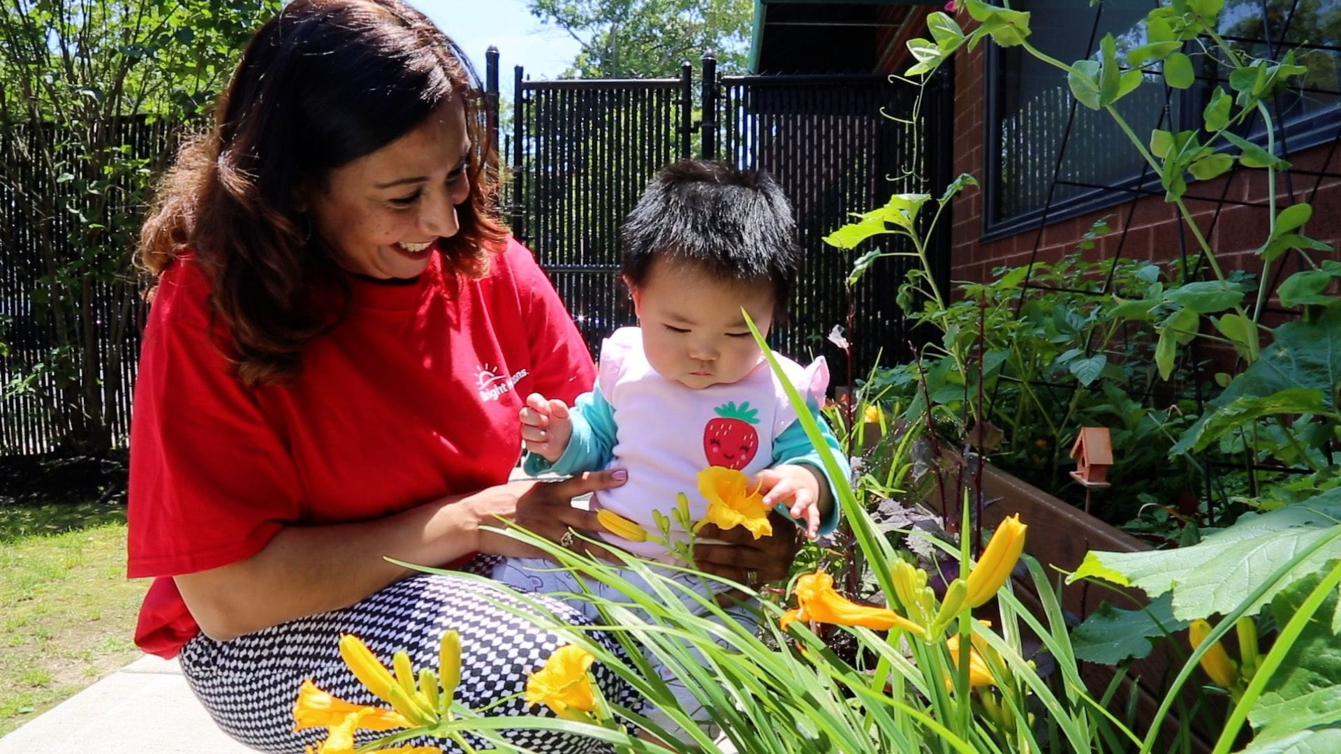 parent with baby looking at flowers