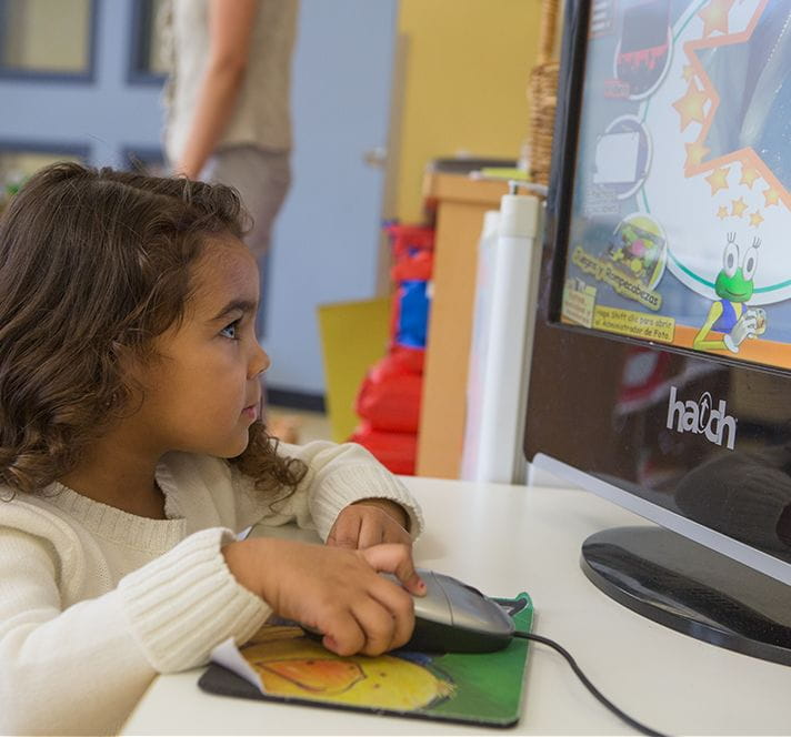 Kindergarten Prep girl with brown hair playing educational games on a desktop computer