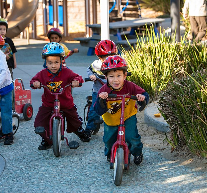Group of young children wearing helmets and riding bicycles outside