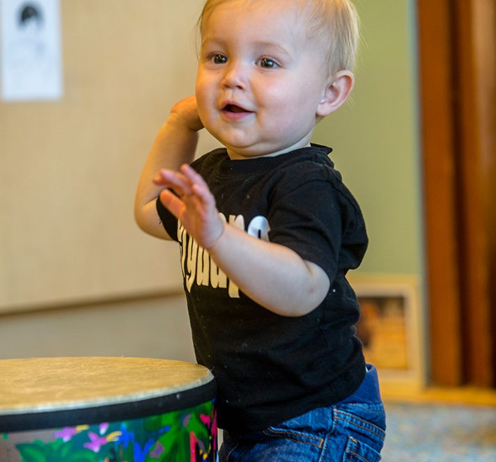 Toddler boy playing with a drum and making music