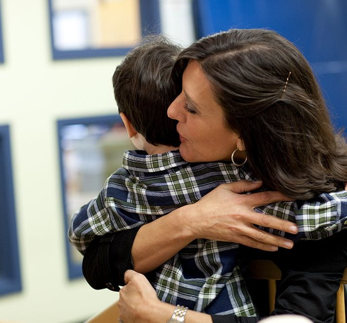 Mom crouching down and hugging her young son at a child care center