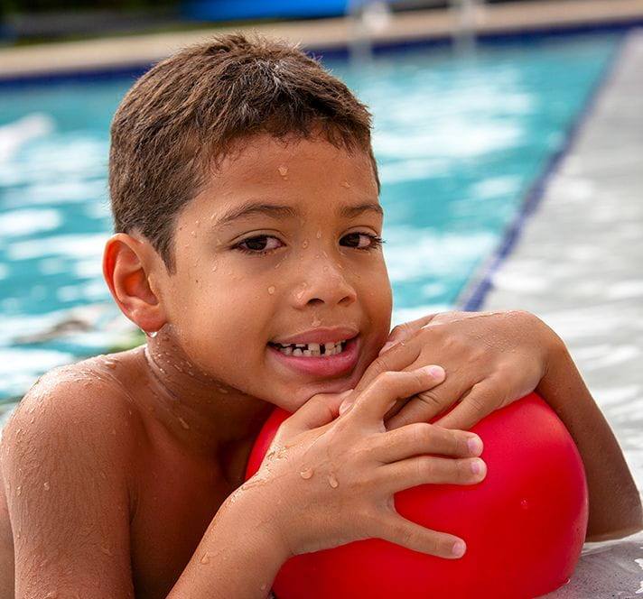 Kindergarten aged boy in a pool hanging on the edge with a red ball in hand