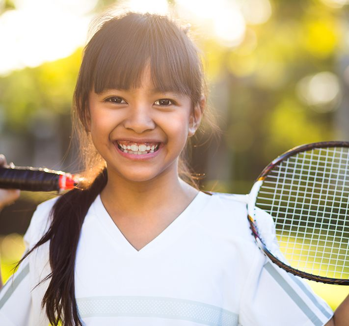 School aged girl with brown hair and bangs in a tennis uniform standing outside with a racquet