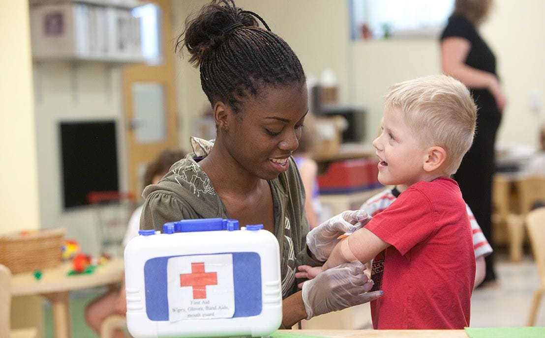 Female teacher putting a bandaid on a preschool boy's arm
