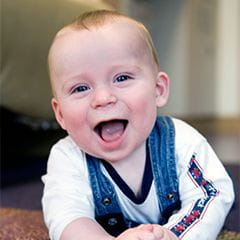 Infant boy crawling and smiling