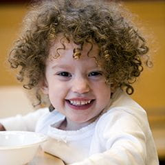 Preschool girl with short, brown, curly hair sitting at a table and smiling