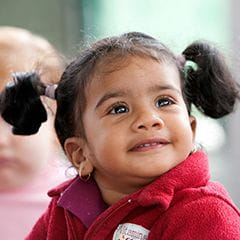 Toddler girl in a pink coat and two pigtails looking up and smiling