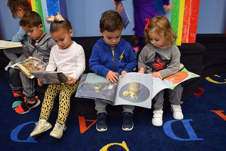 Group of children reading together at Temple Sinai Nursery School