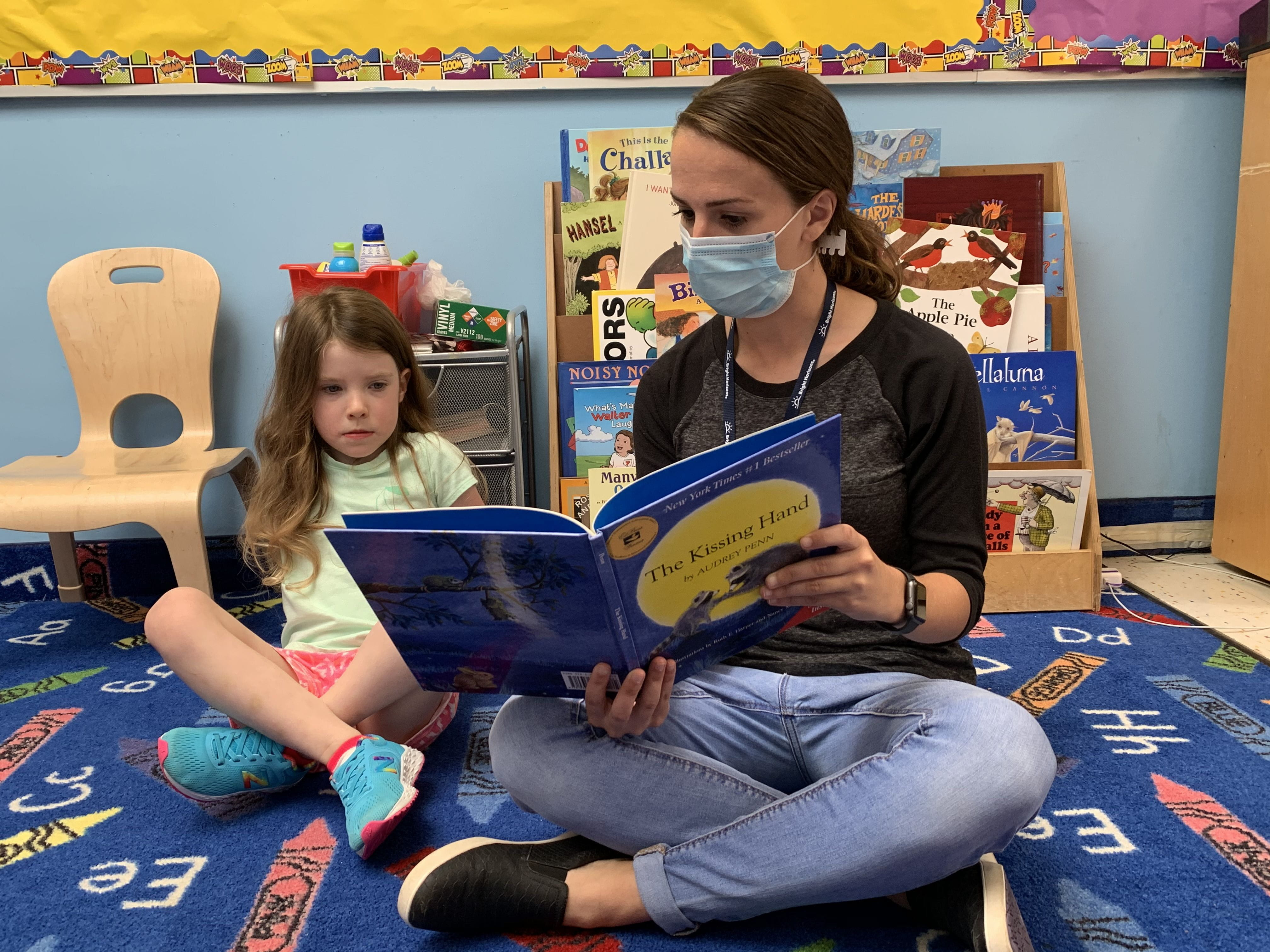 A teacher in a mask reads to a young girl sitting on the floor.