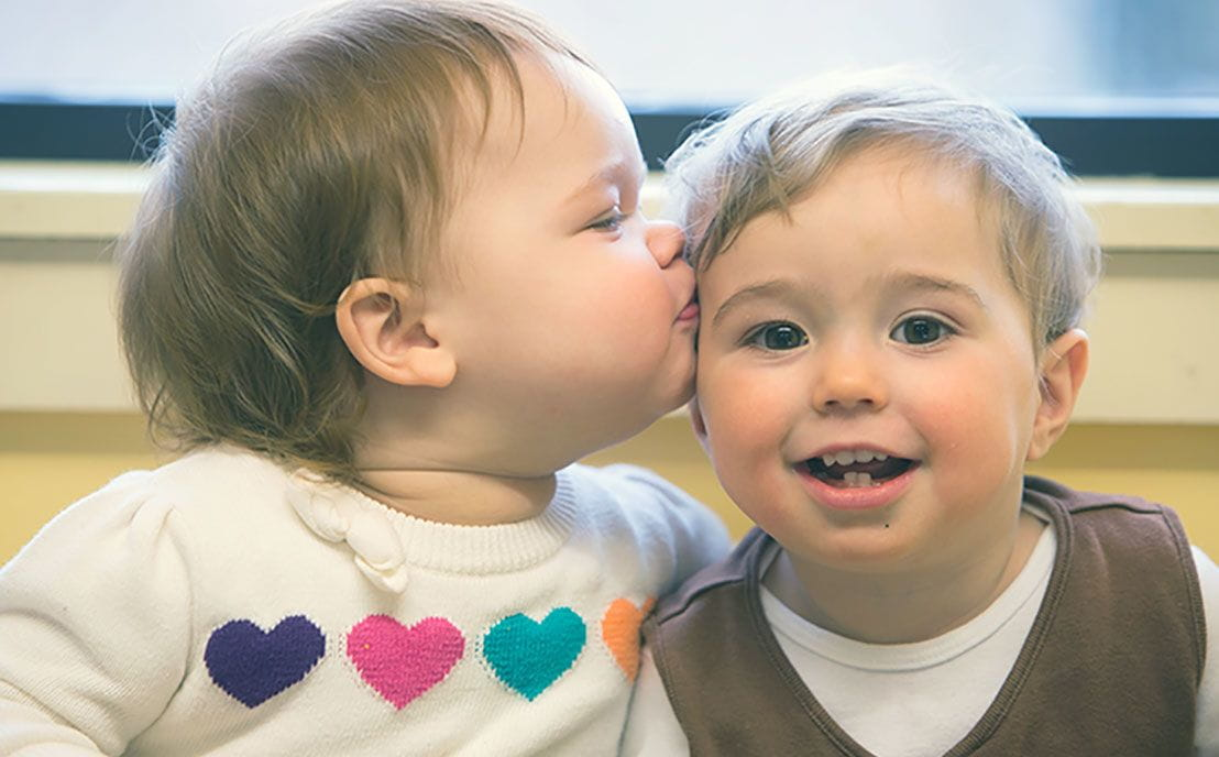 An infant kissing another infant on the cheek