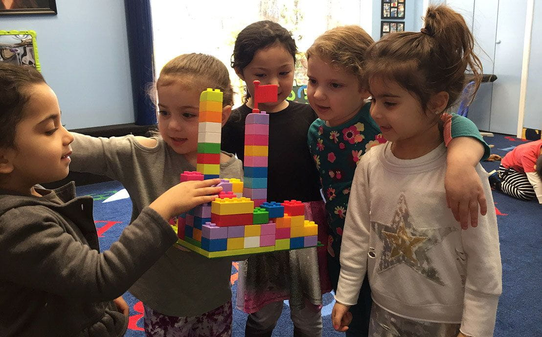 Group of preschoolers building with legos