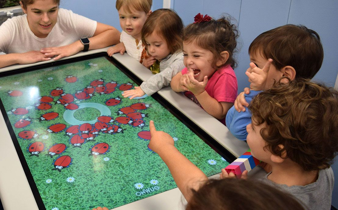 Group of toddlers looking at a game screen