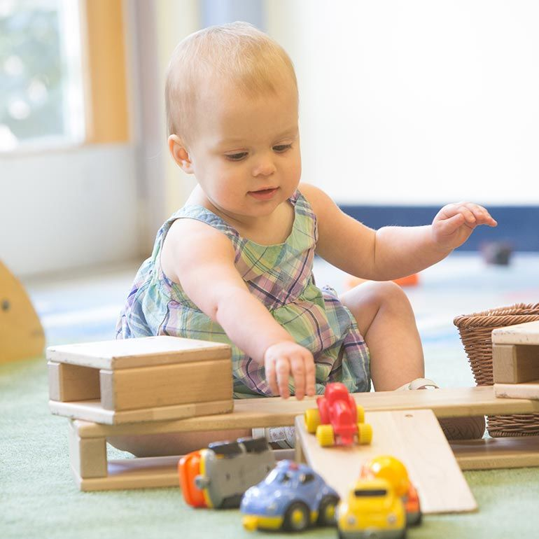 Bright Horizons infant playing with cars and ramps
