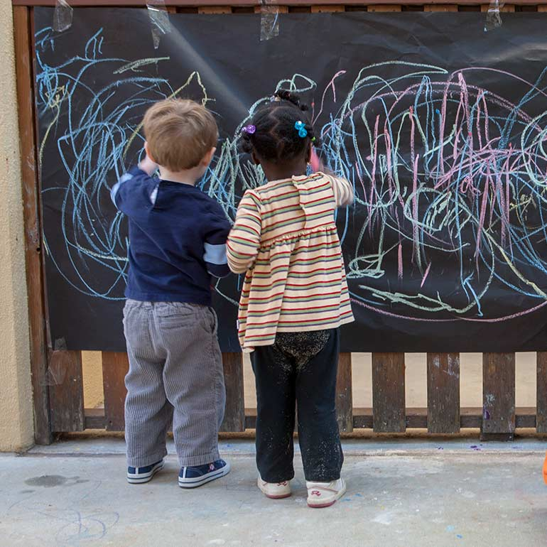 Bright Horizons Toddler Students drawing on the chalk board