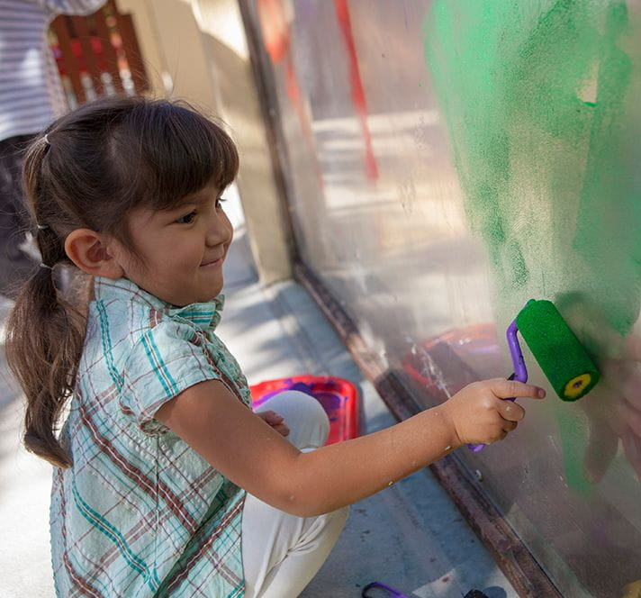 Kindergarten Prep girl with brown hair using a paint roller to paint a mural outside