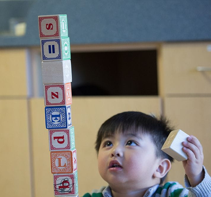 Toddler boy stacking blocks into a tall tower