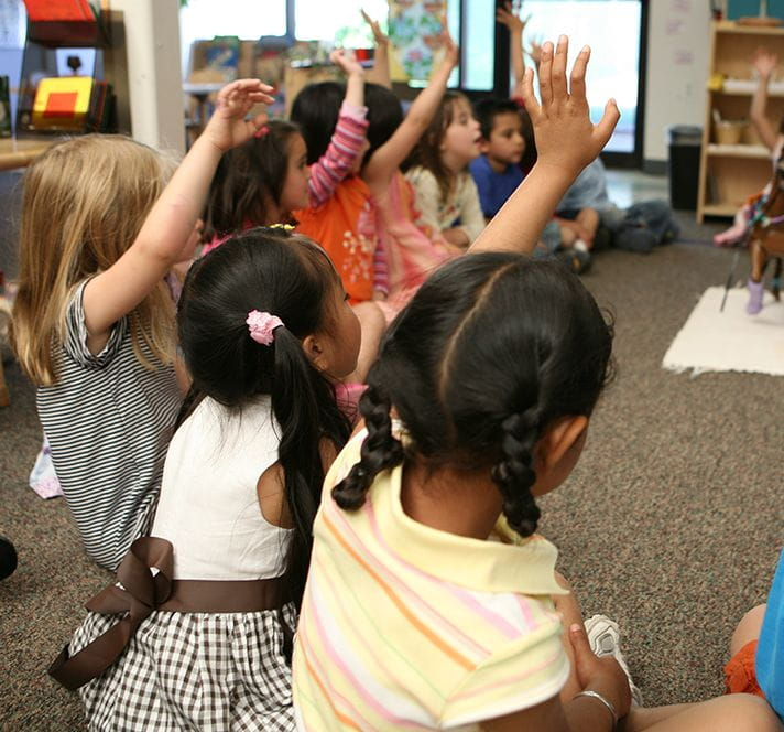 Group of Kindergarten Prep students sitting on the floor in a circle and raising their hands