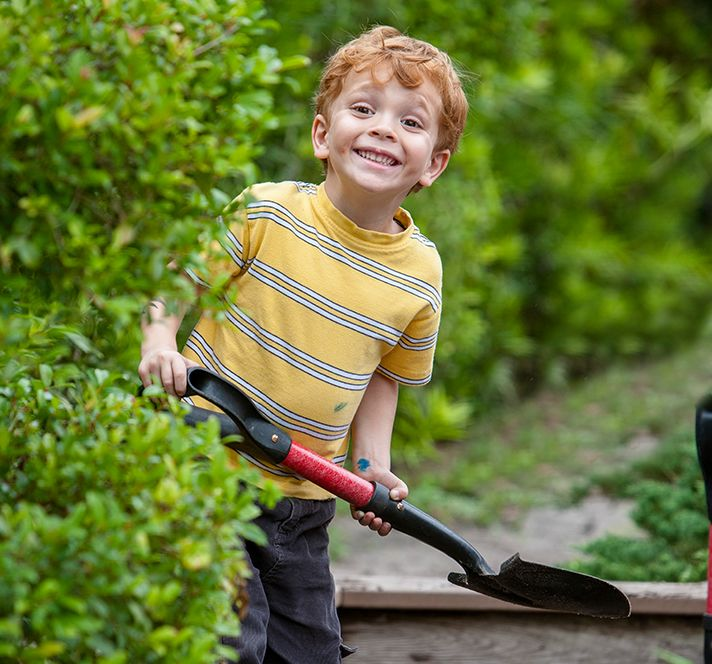Red-haired Kindergarten Prep boy using a spade in the garden outside