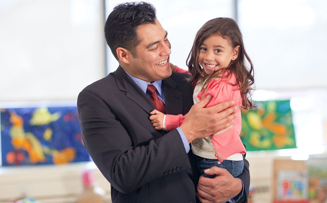 A dad in a suit and tie holding his preschool aged daughter in a child care setting