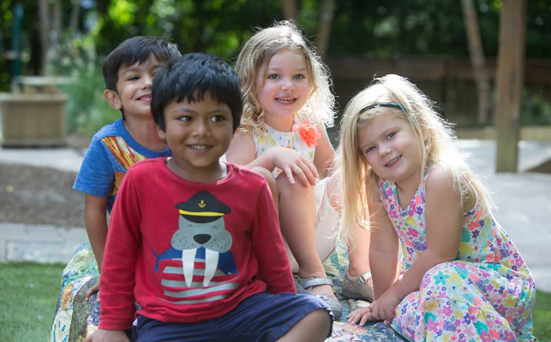 Group of diverse children sitting outside on a rock