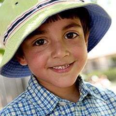 Kindergarten boy wearing a plaid shirt and striped hat outside