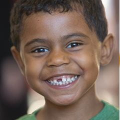 School aged boy with a missing front tooth standing and smiling