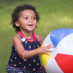 Preschool girl holding a big beach ball outside