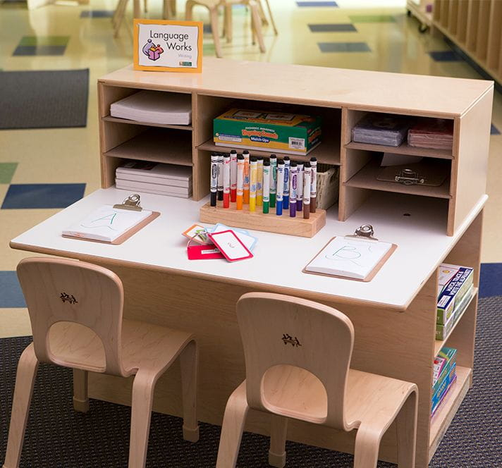 Writing desk in a child care setting with two chairs, paper, and markers