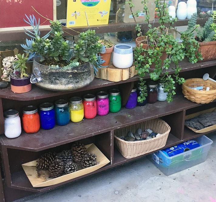 Outdoor shelves with plants, rocks, pinecones, and paint in mason jars