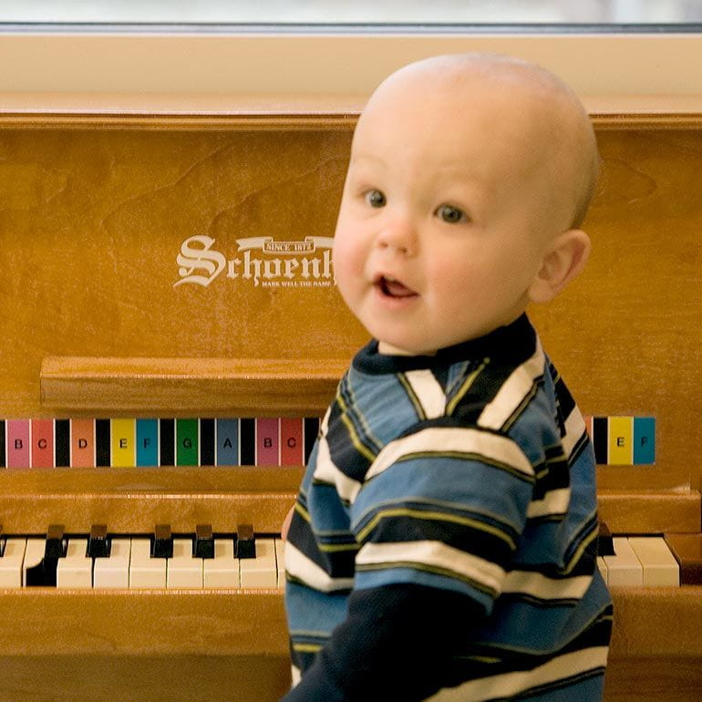 Bright Horizons infant playing with a piano