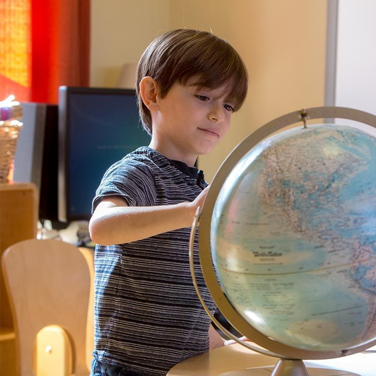 Bright Horizons kindergarten Prep Student studying a globe